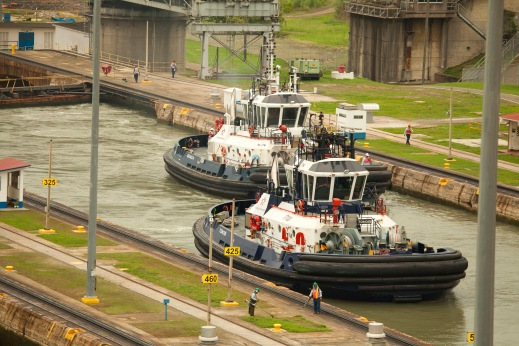big ol' beefy tugs help steer the big ships toward the locks